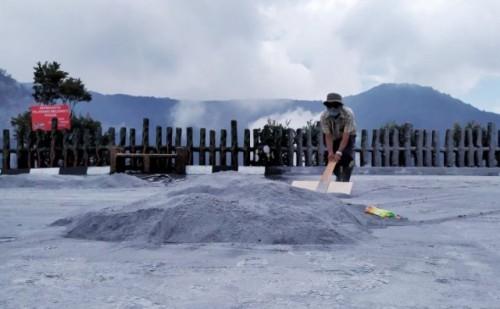 Petugas membersihkan area wisatawan dari abu vulkanik yang menyelimuti Kawah Ratu TWA Gunung Tangkuban Parahu, Sabtu (27/7/2019). (FOto ANT)