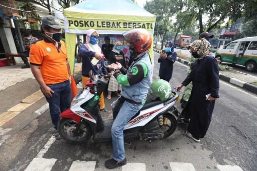 Petugas Posko Lebak Bersatu sedang memeriksa warga yang akan masuk ke wilayah RW 08 Kelurahan Kebonwaru, Kecamatan Batununggal. (Humas)